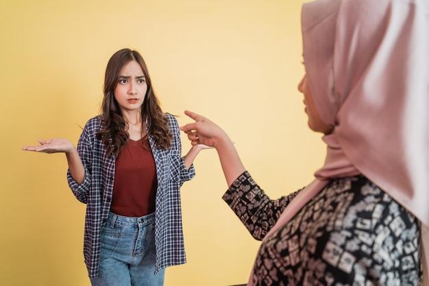 Close up van een aziatische moslimvrouw in hijab wijzende vinger naar vrouw met ontwijkend handgebaar