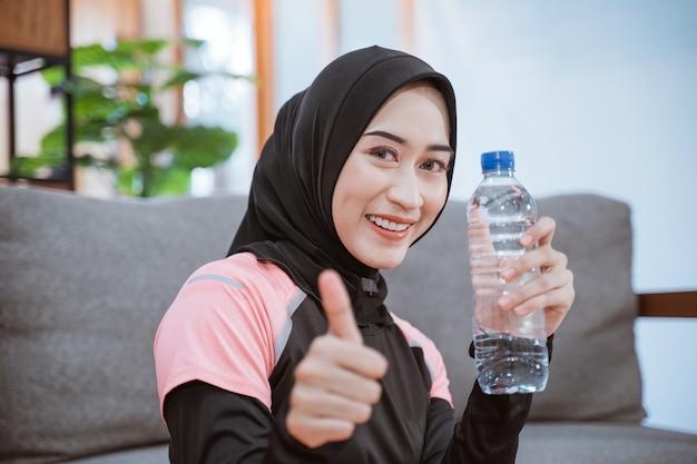 Close-up van een aziatische vrouw in een sluier sportkleding glimlacht terwijl ze een drinkfles met duimen omhoog houdt zittend op de vloer na het sporten binnenshuis thuis