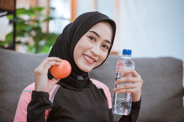 Close up van een aziatische vrouw in een sluier sportkleding glimlacht terwijl ze een drinkfles vasthoudt met handgebaar biedt een appel zittend op de vloer na het sporten binnen