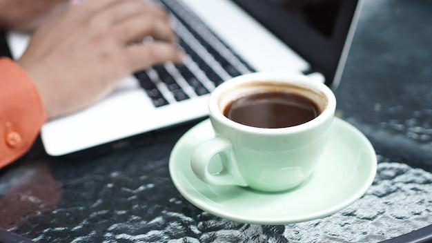 Close-up van een aziatische zakenman die op laptop typt