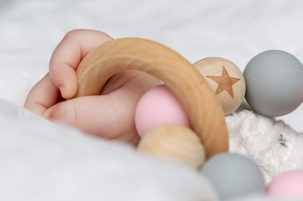 Close-up van een babyhand, spelen met een houten speelgoed.