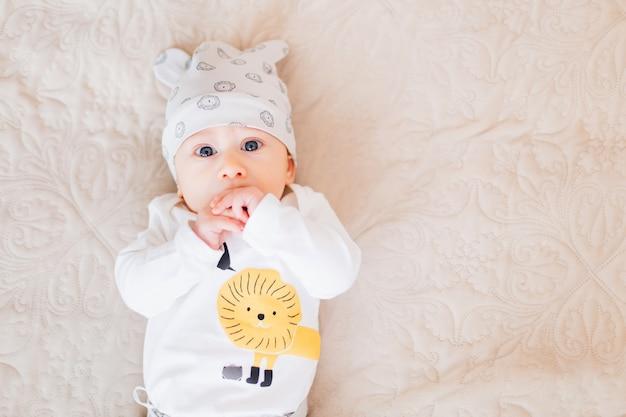 Close-up van een babyjongen die op het bed ligt en hand in hand bij de mond houdt