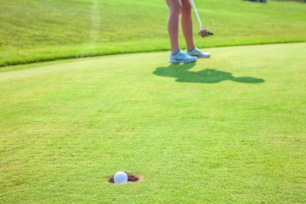 Close-up van een bal in een gat op een golfbaan met een speler