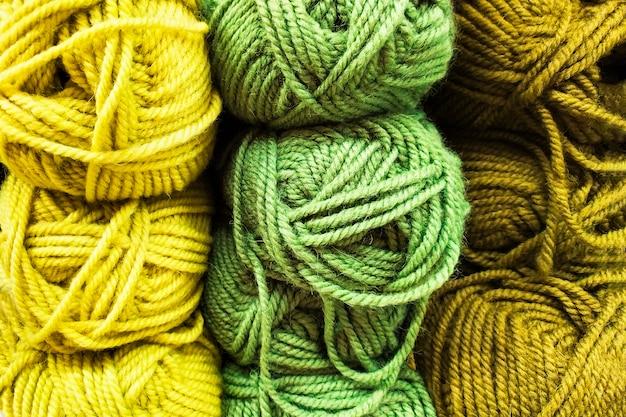 Close-up van een bal van geel, licht en donkergroen wol en katoen veelkleurig garen en draad op een plank in een winkel voor breien en handwerken.