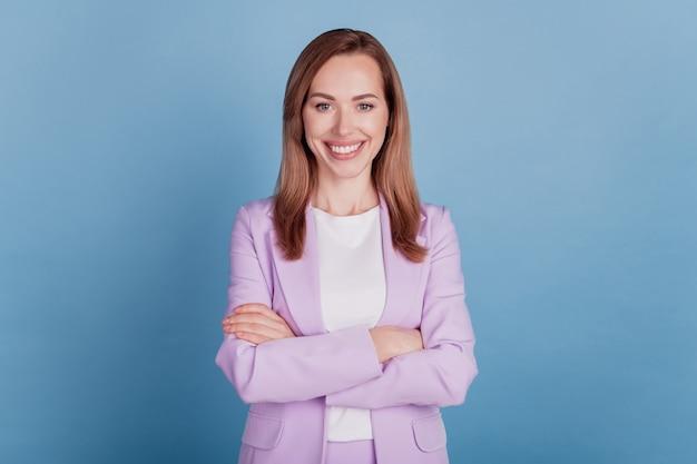 Close-up van een bazige zakelijke dame, een brede glimlach, een camera met gekruiste armen op een blauwe muur