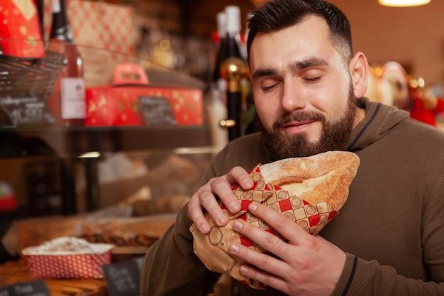 Close up van een bebaarde man lachend met zijn ogen dicht, heerlijk vers brood ruiken bij de bakkerij