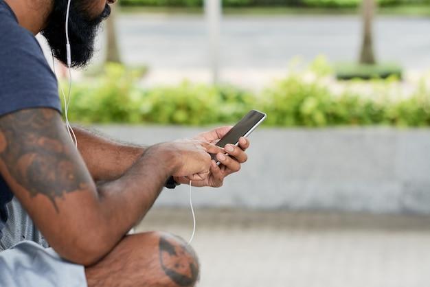Close-up van een bebaarde man met tatoeages die naar audio in oortelefoons luistert en smartphone buitenshuis gebruikt