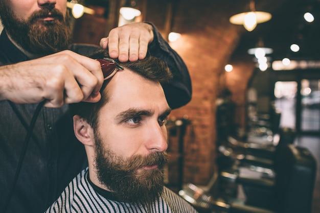 Close up van een bebaarde man. zijn kapper knipt en modelleert zijn haar.