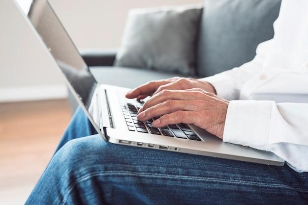 Close-up van een bejaarde die op laptop typt