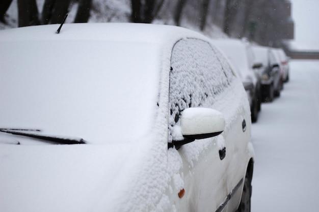 Close-up van een besneeuwde auto op straat in de winter