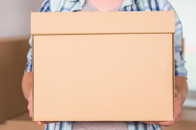 Close-up van een bezorger met kartonnen doos.