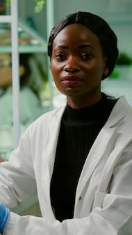 Close-up van een bioloogvrouw die in de camera kijkt terwijl ze in een biologisch agronomisch laboratorium werkt