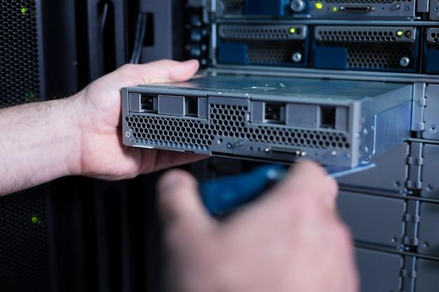 Close-up van een bladeserver die in handen is van een professionele aardige mannelijke technicus terwijl deze in het serverrek wordt geïnstalleerd