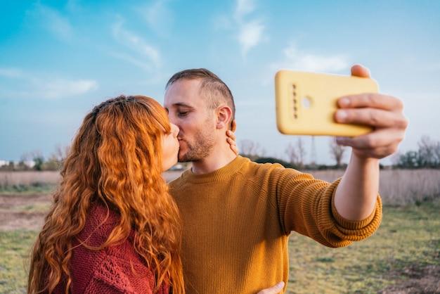 Close-up van een blank stel dat een selfie neemt in een veld terwijl ze verliefd zoenen