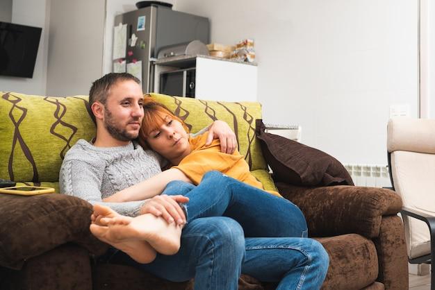 Close-up van een blank stel dat thuis op de bank omhelst terwijl ze televisie kijkt