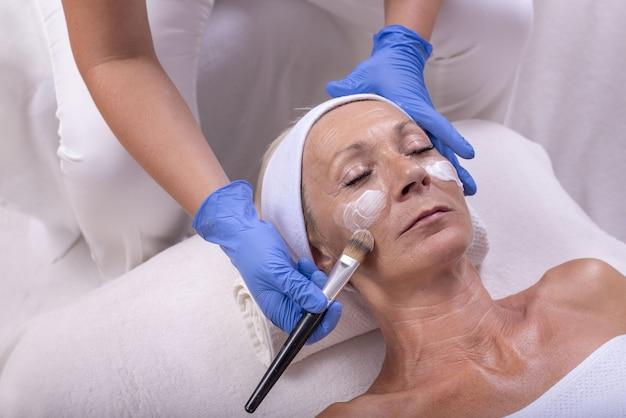 Close-up van een blanke oudere vrouw die gezichtscrème aanbrengt in een schoonheidssalon
