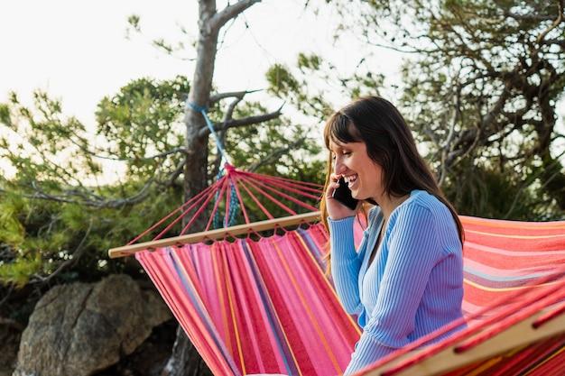 Close-up van een blanke vrouw die lacht aan de telefoon die in een hangmat zit