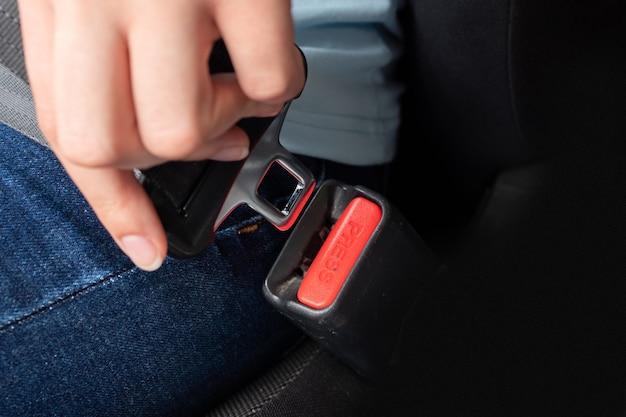 Close-up van een blanke vrouwelijke hand met een veiligheidsgordelgesp voor bevestiging in een auto.