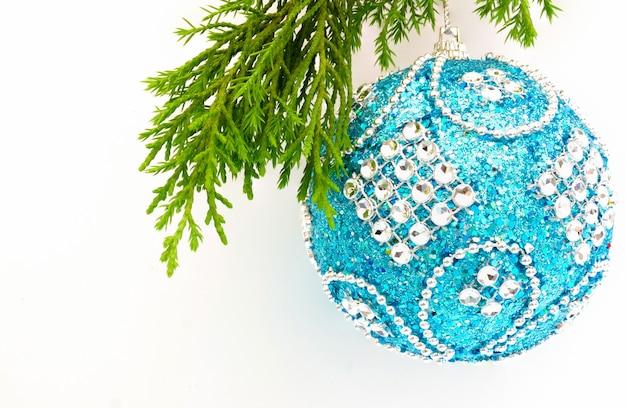 Close-up van een blauwe kerstbal die aan een takje van een groenblijvende boom hangt