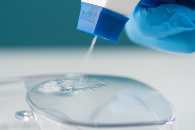 Close-up van een blauwe spuitfles die een chemische oplossing op plastic glazen sproeit om de productvernietiging van ziektekiemen en bacteriën op een geïnfecteerd object te desinfecteren