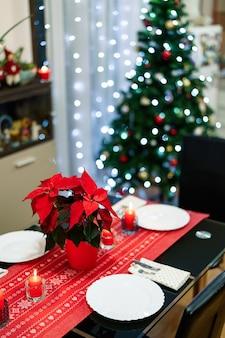 Close-up van een bloem in een rode pot op een feestelijk versierde tafel voor de nieuwe jaarvakantie Premium Foto