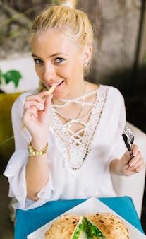 Close-up van een blonde jonge vrouw die aardappelfrieten eet