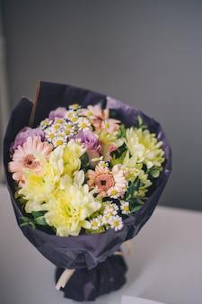 Close-up van een boeket van kleurrijke bloemen in paarse verpakkingsst