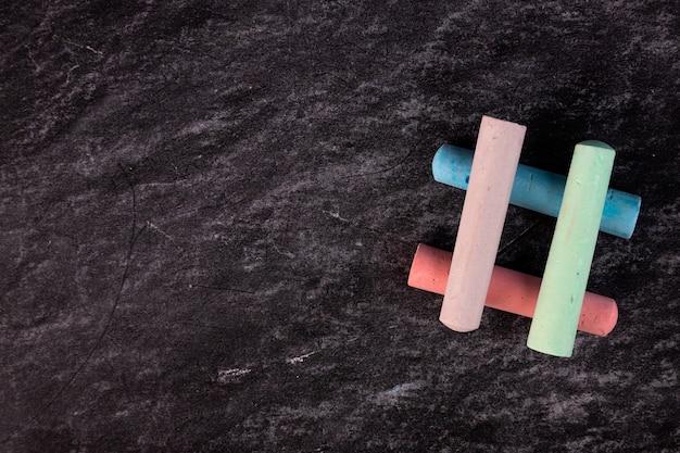 Close-up van een bord met stukjes gekleurd krijt in de vorm van een hashtag.
