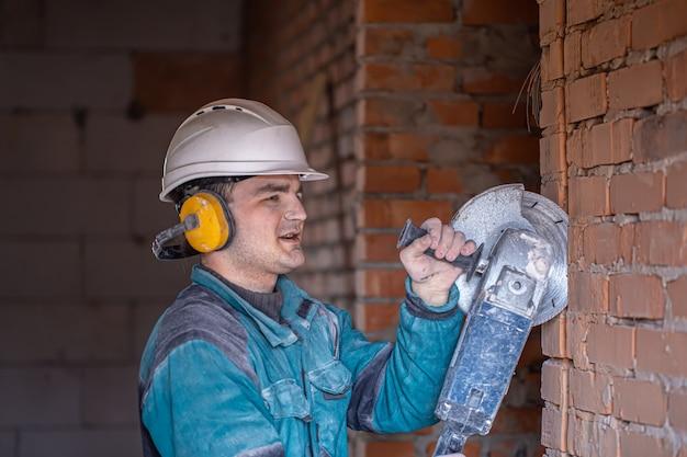 Close-up van een bouwer in een beschermende helm op een werkplek werkt met een snijgereedschap.