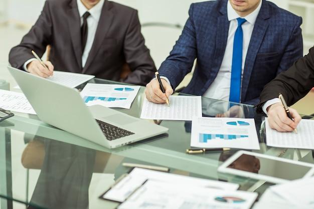 Close-up van een business team dat analyse van marketingrapporten uitvoert op de werkplek op kantoor.