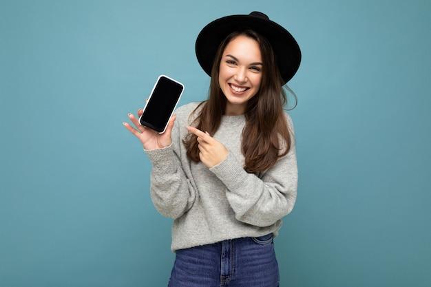 Close-up van een charmante jonge gelukkige vrouw met een zwarte hoed en een grijze trui met een telefoon die naar