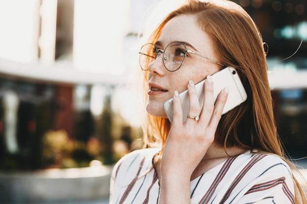 Close up van een charmante jonge vrouwelijke ondernemer met rood haar en sproeten praten aan de telefoon buiten tegen een gebouw.