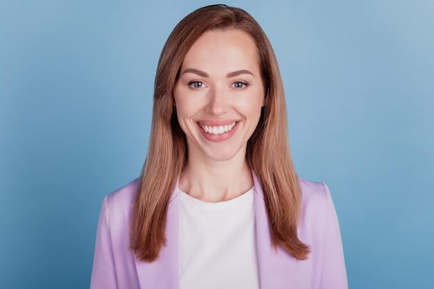 Close-up van een charmante zakenvrouw kijkt camera met een stralende witte glimlach