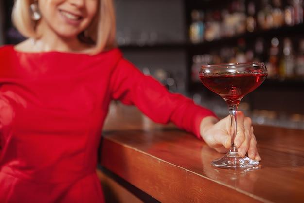 Close up van een cocktailglas in de handen van vrolijke elegante vrouw in rode jurk. vrouw drinken aan de bar