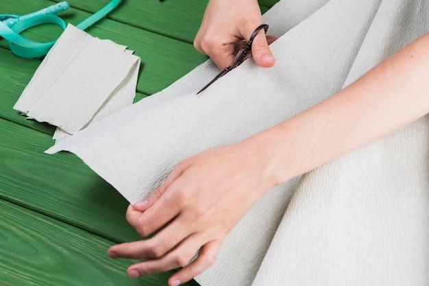 Close-up van een crêpepapier van de vrouwenknipsel met schaar