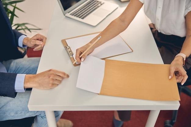Close-up van een dame die een vel papier uit de kantoorenvelop trekt terwijl ze tegenover de man aan de tafel zit