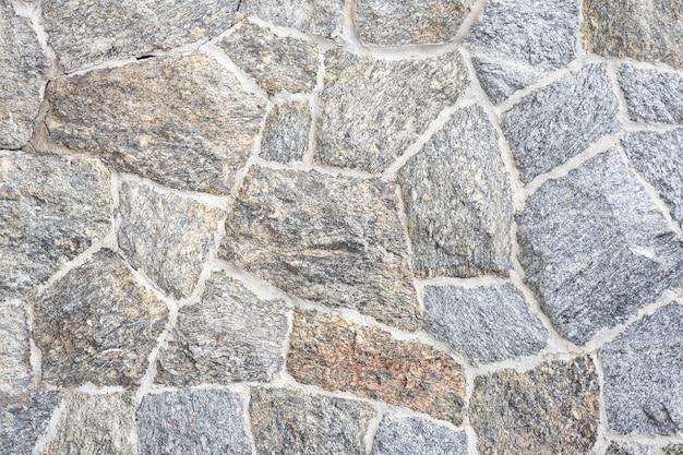 Close-up van een deel van een stenen muur rustieke grunge naadloze textuur achtergrond