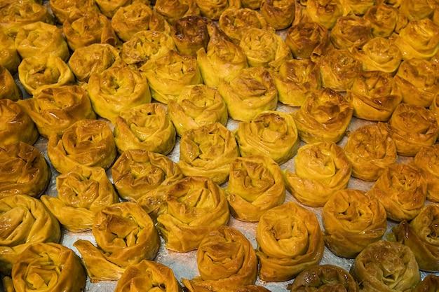 Close up van een dienblad met vers gebakken zoete broodjes. heerlijke en smakelijke zoete lekkernijen op een bakplaat. banketbakkerij die bruinachtig gebak verkoopt. gezoete broodjes kopen en eten.