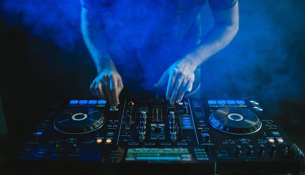 Close-up van een dj die onder het blauwe licht werkt