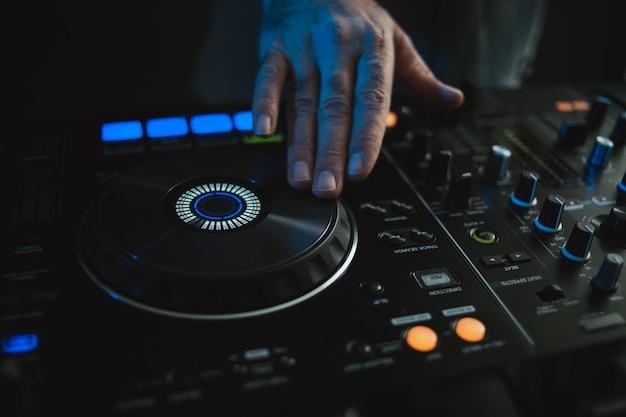 Close-up van een dj die werkt onder de kleurrijke lichten in een studio met een wazig