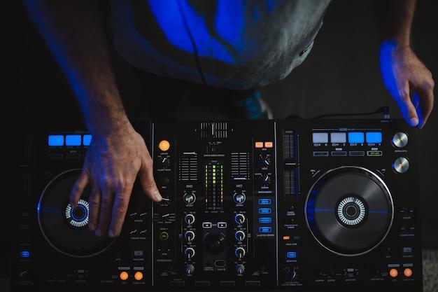 Close-up van een dj die werkt onder de kleurrijke lichten in een studio