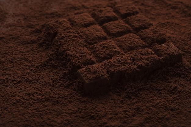 Close-up van een donkere chocoladereep bedekt met chocoladepoeder