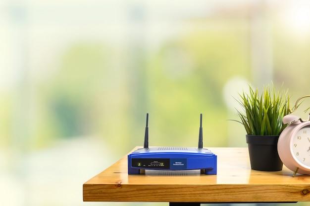 Close-up van een draadloze router en een mens die smartphone op woonkamer thuis bureau gebruiken