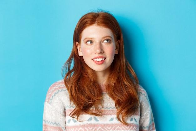 Close-up van een dromerig roodharig meisje dat iets afbeeldt, naar de rechterbovenhoek staart en glimlacht, staande in de wintertrui tegen een blauwe achtergrond