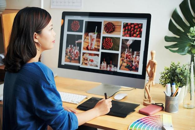 Close-up van een drukke jonge aziatische ontwerper die aan een houten bureau zit met een kleurstaal en een digitizer gebruikt tijdens het retoucheren van foto's