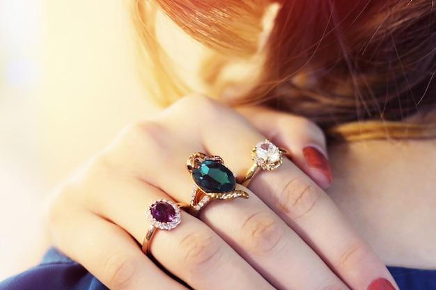 Close up van een elegante ring met stenen op handen van de vrouw. concept rijkdom, juwelen. veel ringen op de vingers.