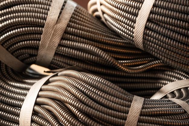 Close-up van een enorme gouden bundel van flexibele metalen buizen die in een fabriek of fabriek met elkaar zijn verbonden. het concept van moderne militaire en industriële productie.