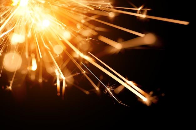Close-up van een fel oranje vuur van een brandend sterretje brandt in het donker