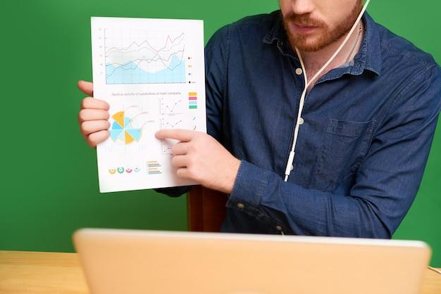Close-up van een financieel adviseur in oortelefoons die naar de grafiek wijst terwijl hij statistische gegevens aan de klant uitlegt en met hem praat via videoconferenties