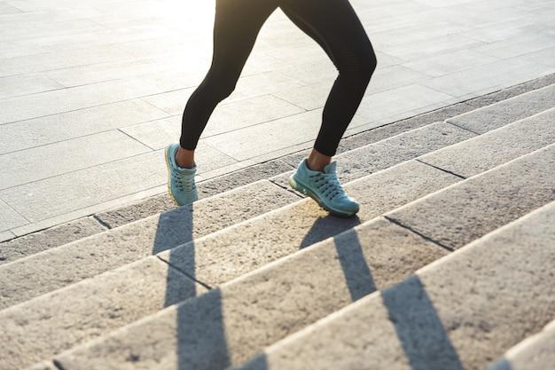 Close up van een fitness vrouw joggen de trap buitenshuis